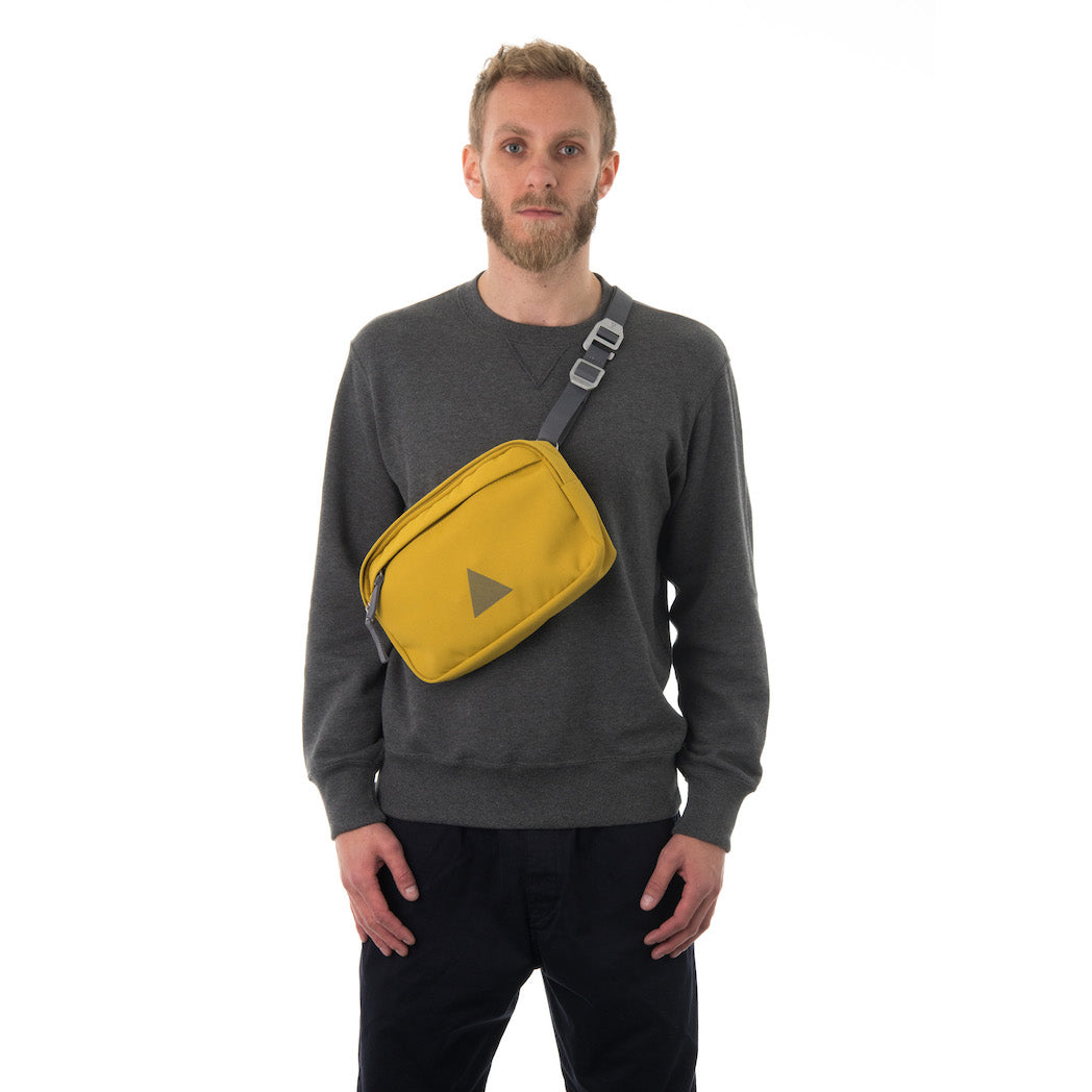 Man wearing yellow cross body bag.