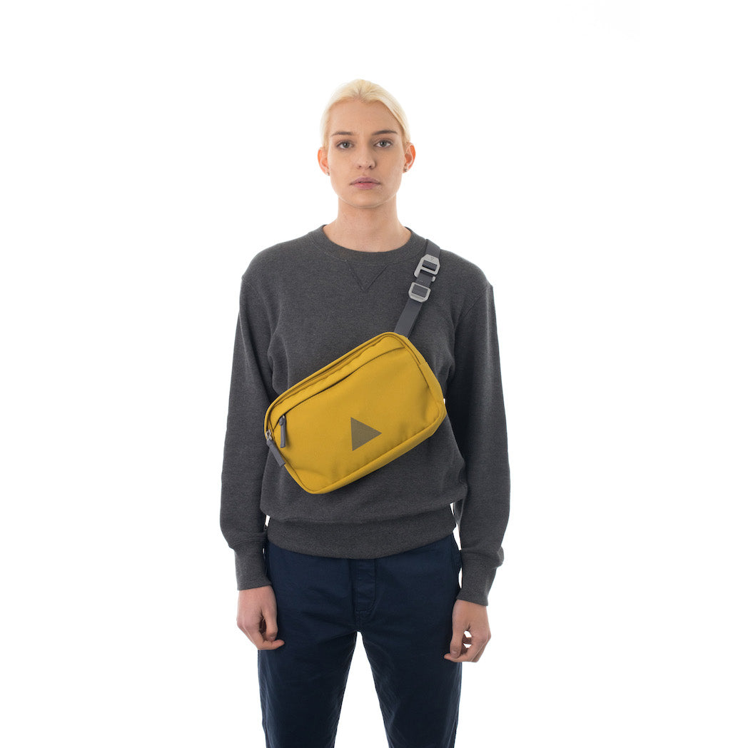 Woman wearing yellow cross body bag.