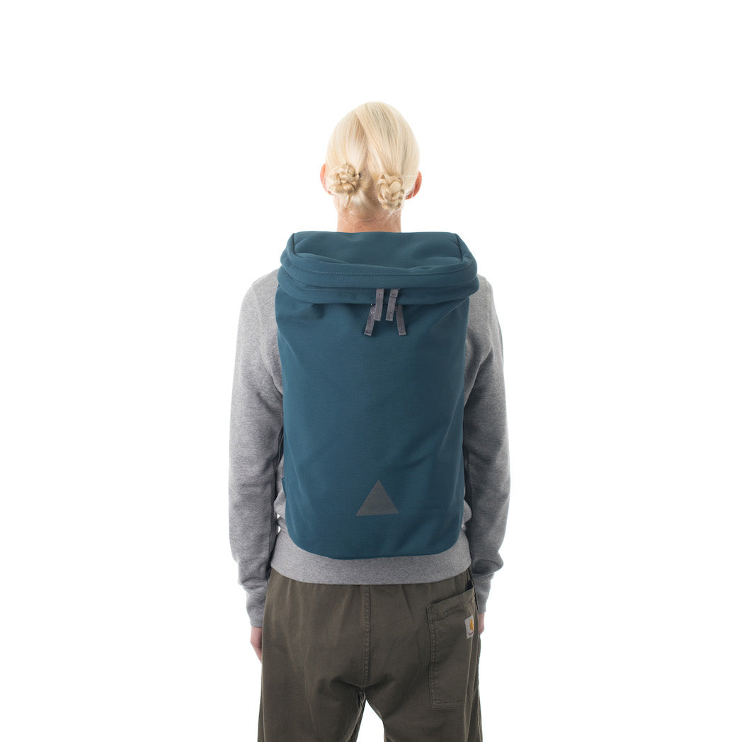 Woman wearing large blue backpack with triangle logo.