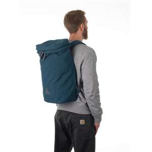 Man wearing large blue canvas backpack.
