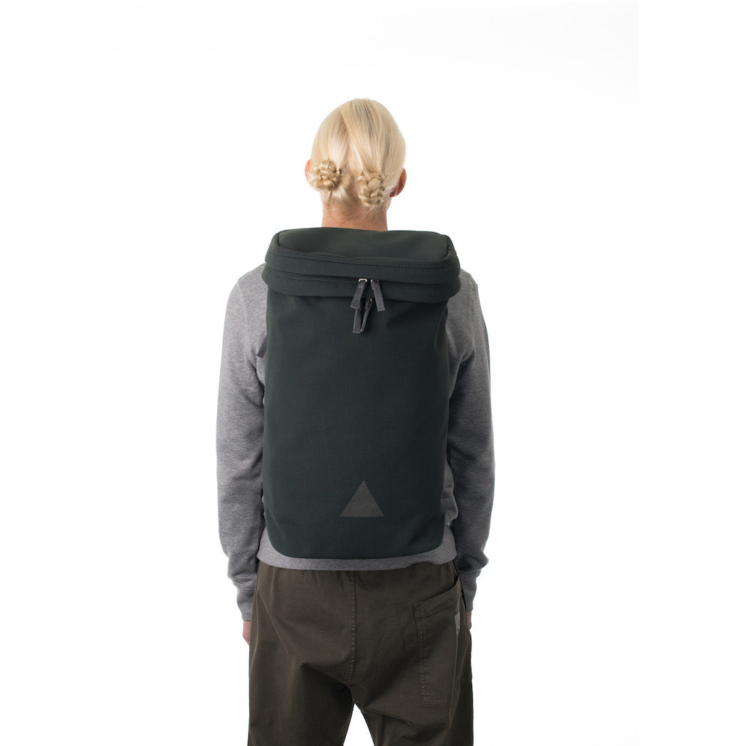 Woman wearing large grey backpack with triangle logo.