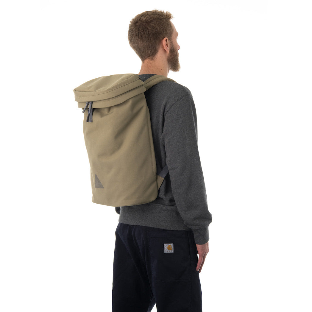Man wearing large khaki canvas backpack.