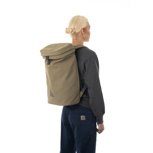 Woman wearing large khaki backpack.