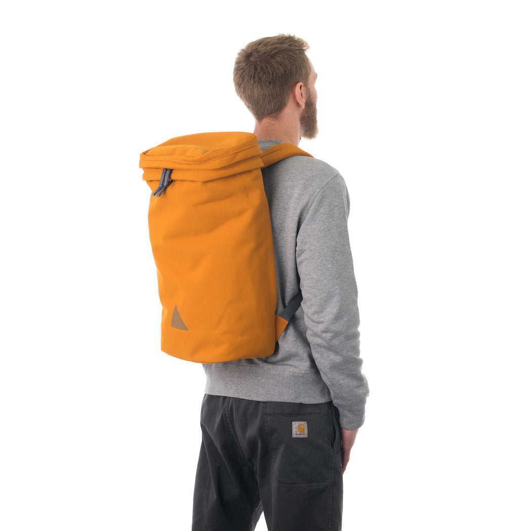Man wearing large orange canvas backpack.