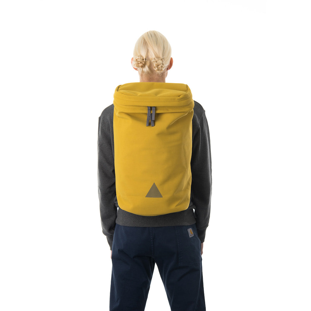 Woman wearing large yellow backpack with triangle logo.