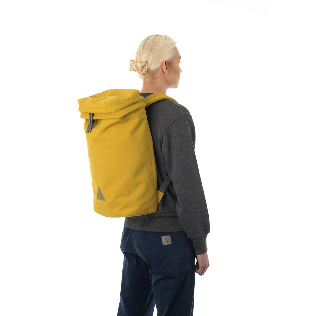 Woman wearing large yellow canvas backpack.