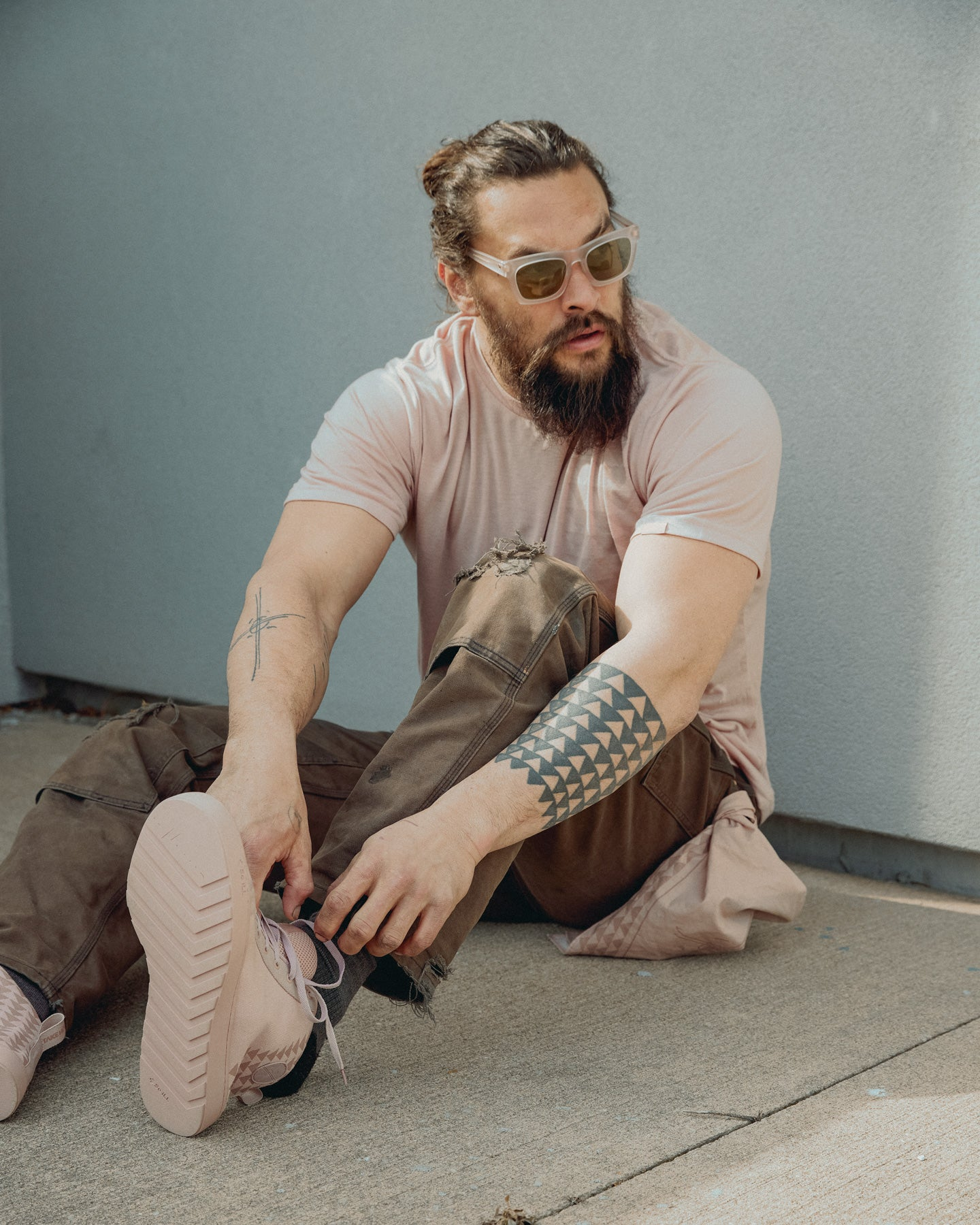 Jason Momoa tries on a pair of So iLL shoes while a bandana hangs from his side