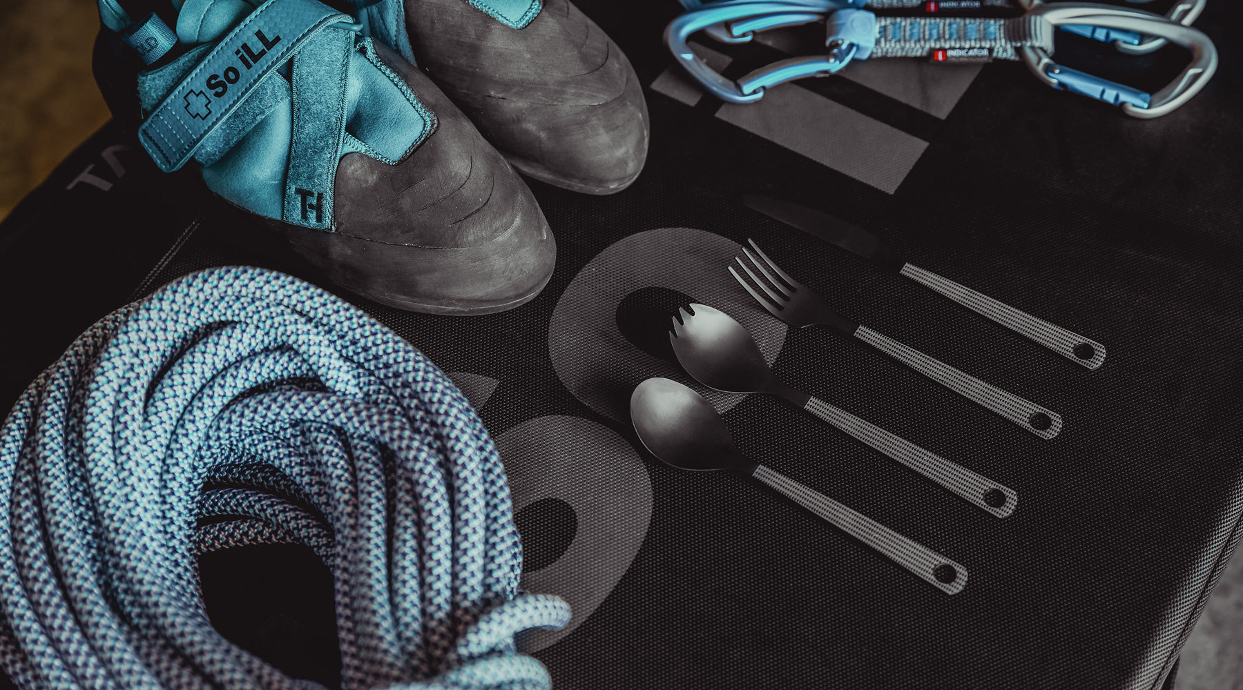 So iLL x On The Roam cutlery shown on a crash pad Distribution brush 2.0 is shown on a climbing mat with climbing chalk