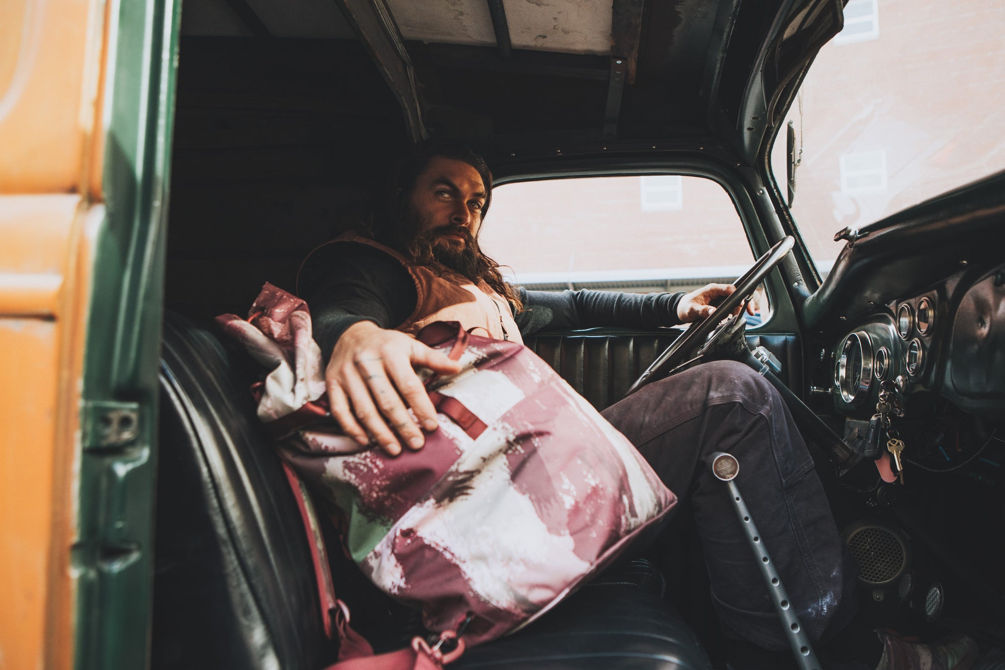 Jason Momoa is shown in an old car holding the So iLL x On The Roam eco camo 45L dirt bag is shown at elephant rocks state park
