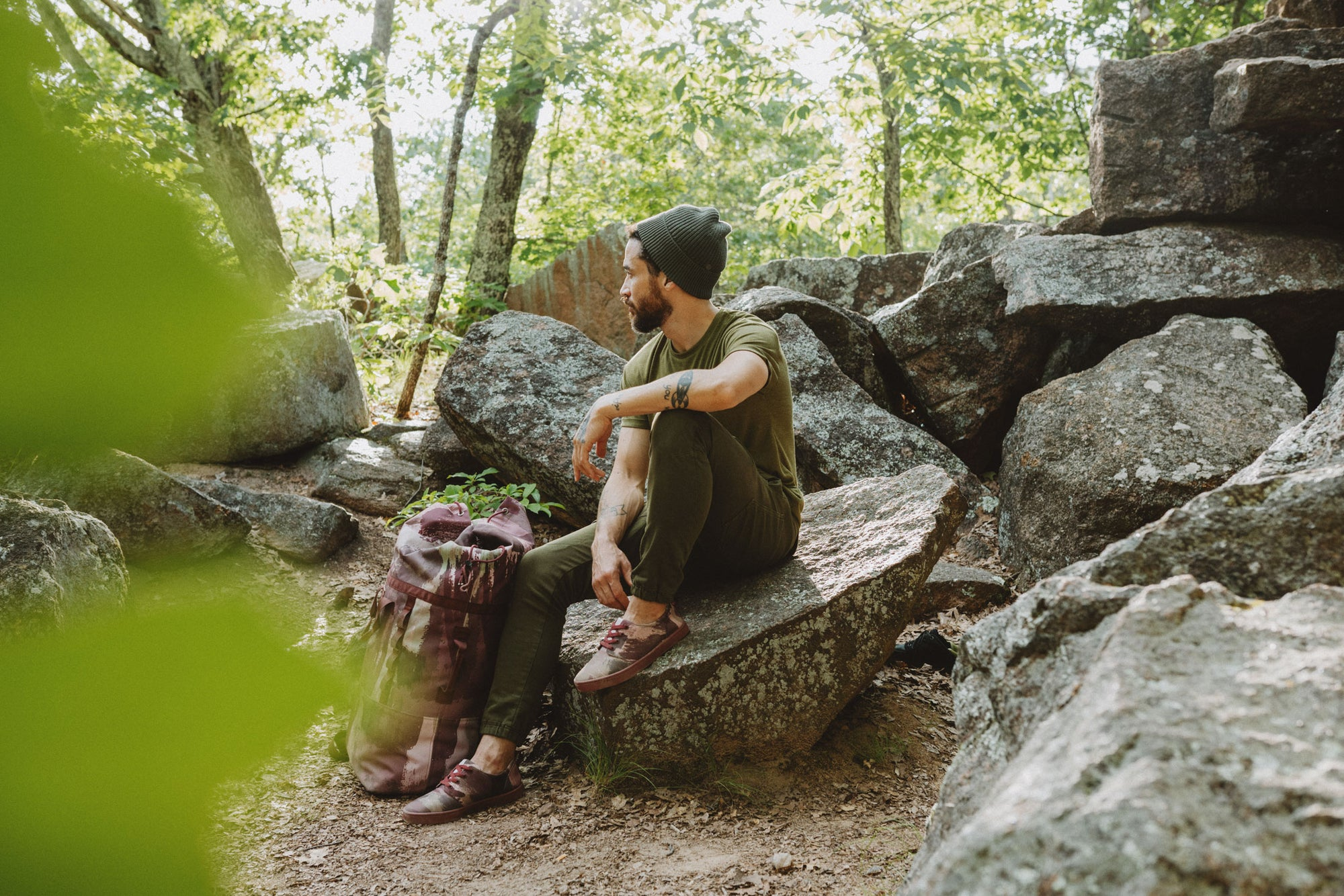 a man sits on a rock with the So iLL x On The Roam eco camo 45L dirt bag