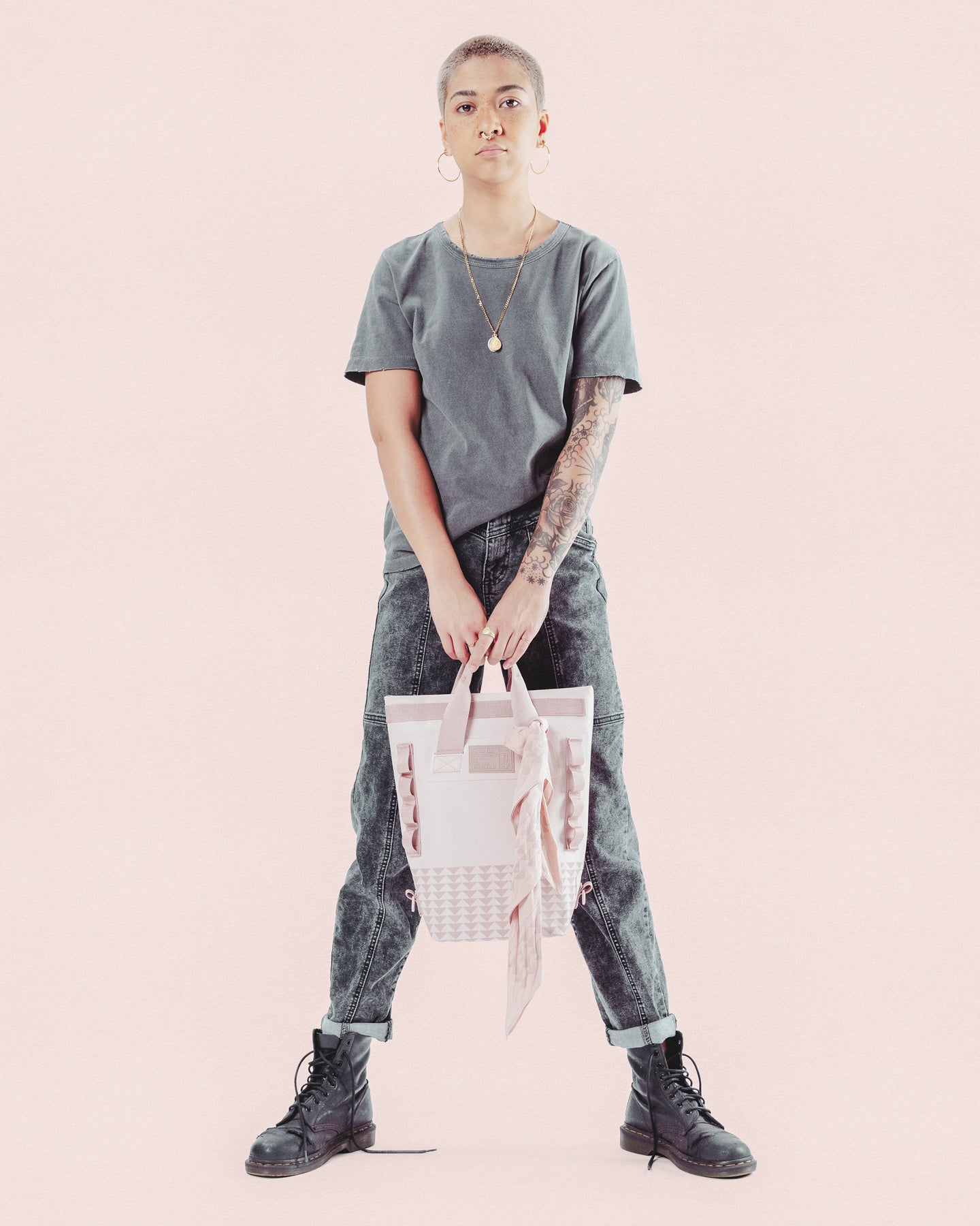 A female model uses the pink so ill bandana as an accessory for her bag