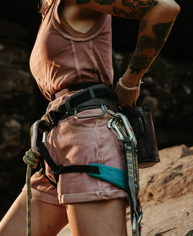 a woman is pictured with a climbing harness and gear on while putting her hands in the so ill x on the roam black chalk bag