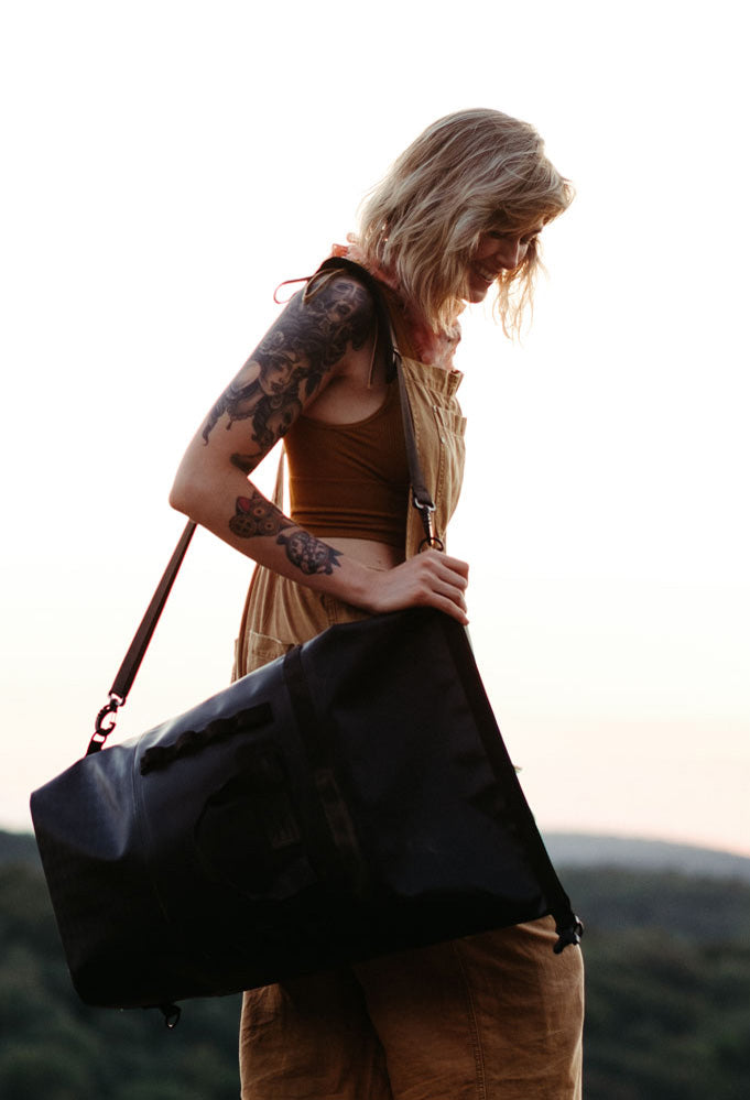 A woman carries the 45 liter black dirtbag on a climbing trip