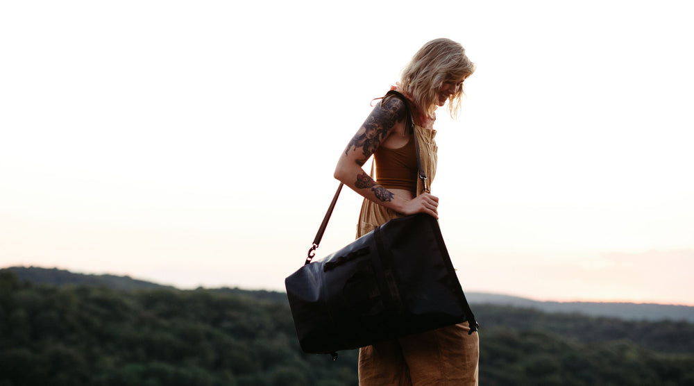 woman is shown with a the so ill x on the roam 25L dirt bag and a mountainous background