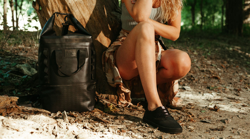 Black wolf wino shoe is shown on a female model in the forest