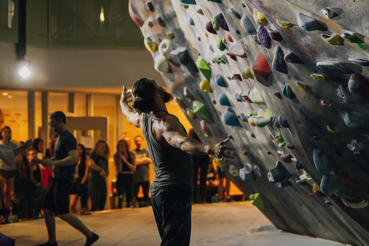 actor and climber jason momoa sizes up a climbing wall at a climbing even at climb so ill