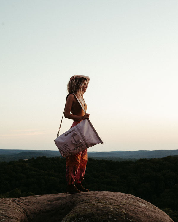 a woman overlooks a scenic range while wearing jason momoa's dirty pink dirt bag - a so ill and on the roam collaboration