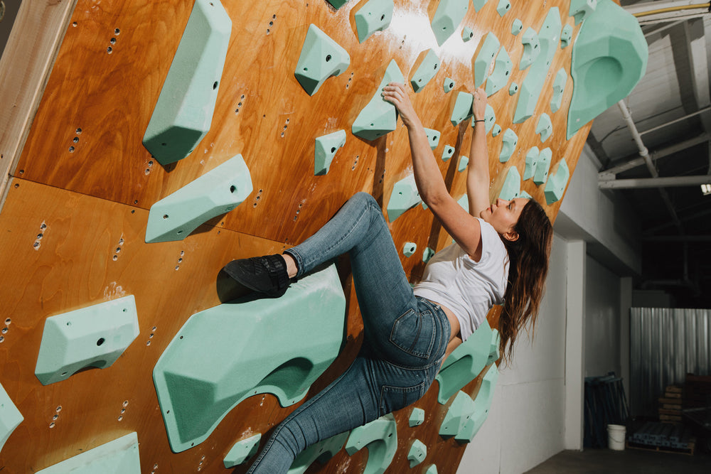 A woman wears the black momoa pro climbing shoes while climbing on so ill climbing holds
