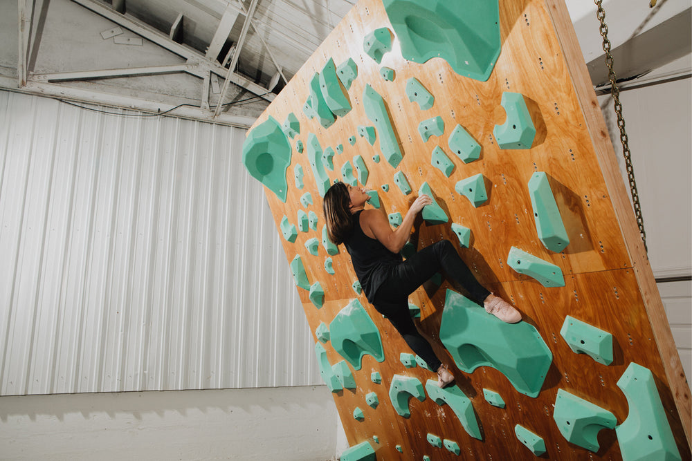 A woman climbs with the so ill x on the roam momoa pro lv shoes  on so ill climbing holds