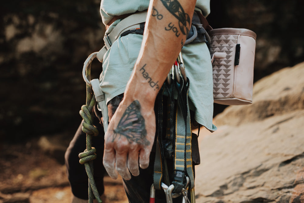 a man with a climbing harness and gear on is shown wearing the pink so ill x on the roam chalk sac