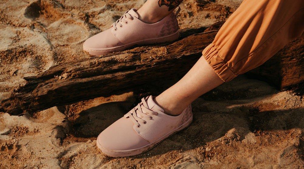 So iLL x On The Roam Jason Momoa Collection Dirt Pink Wino Shoes shown being worn, resting on a log and rocks.