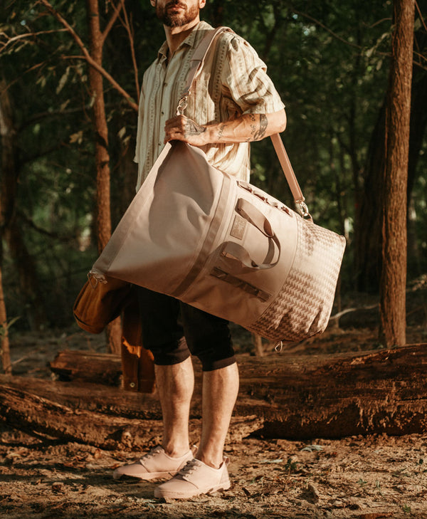 so ill x on the roam jason momoa collaboration shoes and bag are pictured being held/worn by a man in the woods