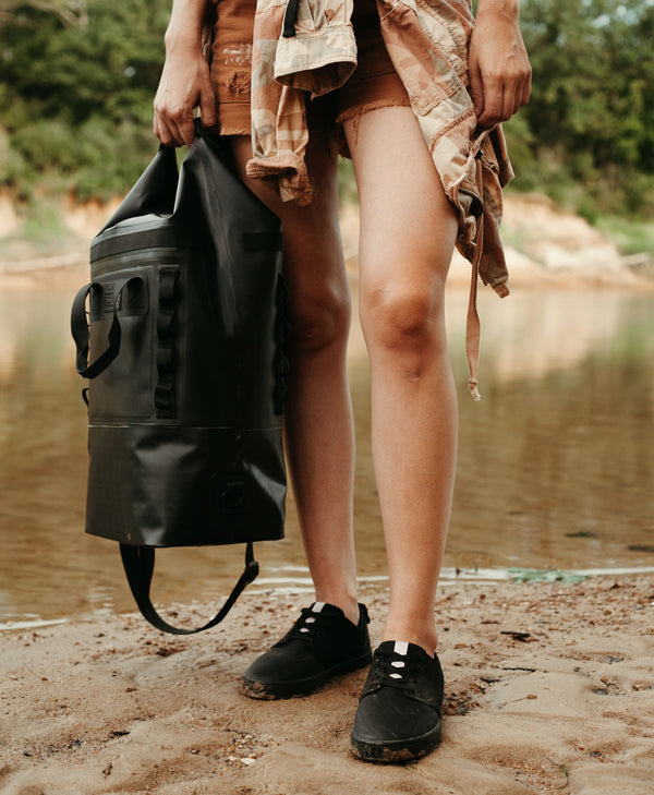 so ill x on the roam jason momoa collaboration shoes and bag are pictured near a river and being held/worn by a young lady