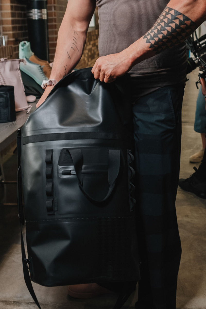 on the roam and so ill collaboration by jason momoa holding 45L medium black bag