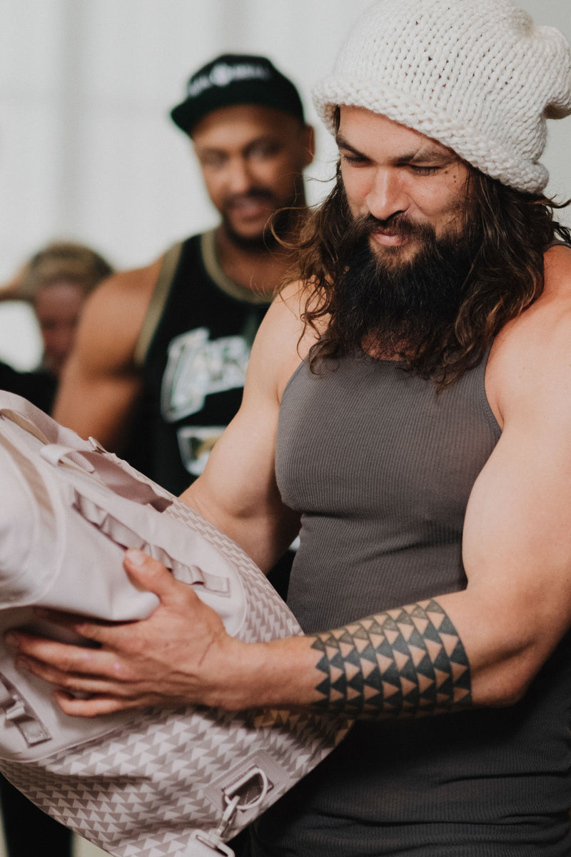 on the roam and so ill collaboration by jason momoa holding 45L medium pink bag