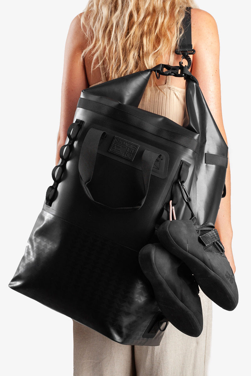 on the roam and so ill collaboration by jason momoa 45L medium black bag on female model with climbing shoes