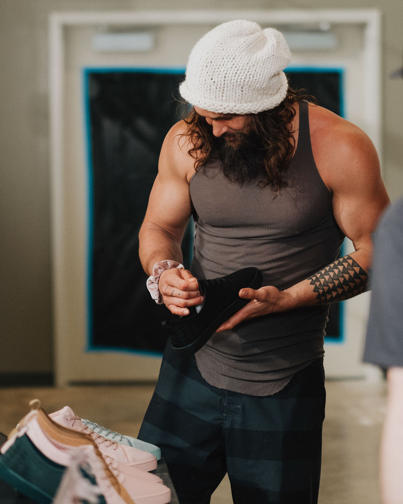 on the roam and so ill collaboration by jason momoa holding black wolf wino shoe