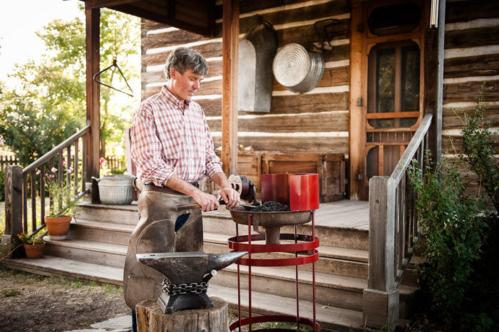 Tuli Fisher working outside to create his hand crafted garden tools of Fisher Blacksmithing