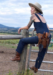 Woman leaning on fence wearing leather toolbelt