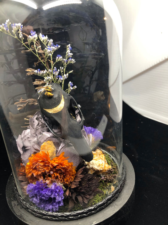 Rat skull with orange calcite, dried flowers inside a glass dome.