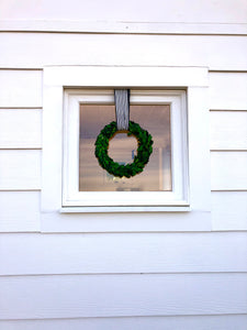Hanging boxwood wreaths in windows
