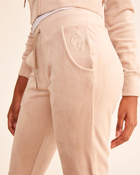 Taupe velour jogger pant with stretch velvet fabric, front pockets, metal tipped drawstrings, and elasticized waistband and leg openings. Features tonal cat embroidery at hip. Semi-fitted.