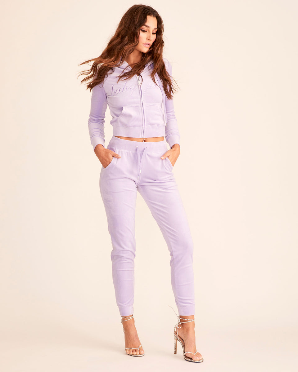 Lavender velour jogger pant with stretch velvet fabric, front pockets, metal tipped drawstrings, and elasticized waistband and leg openings. Features tonal cat embroidery at hip. Semi-fitted.