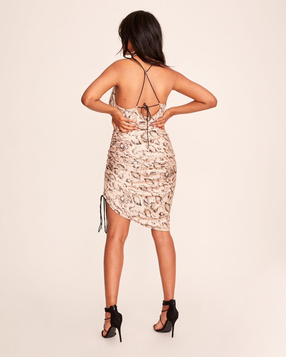 Python print silky cowl neck dress with string tie detail and ruched fabric. Contrasting black strings and an open back. Dress features silver Baby Phat cat logo charms on the strings.