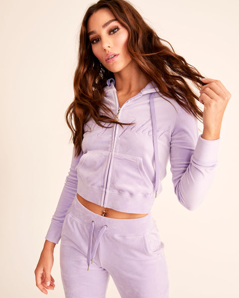 Lavender velour track jacket and hoodie with front zip. Features metal cat charm on zipper pull, embroidered tonal Baby Phat logo across the chest, embroidered tonal cat logo on the back, kangaroo pockets, elasticized waistband and cuffs.