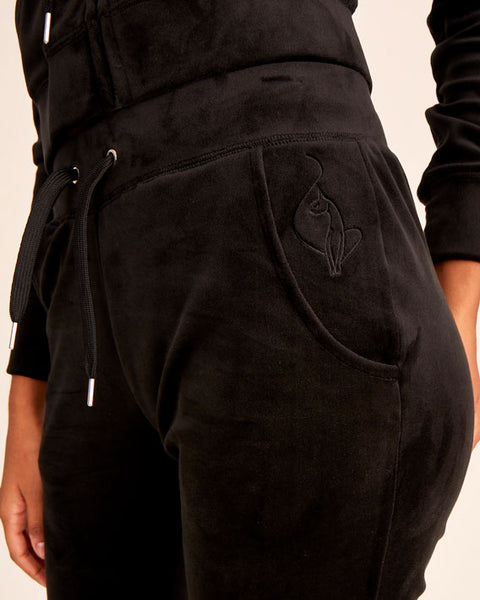 Black velour jogger pant with stretch velvet fabric, front pockets, metal tipped drawstrings, and elasticized waistband and leg openings. Features tonal cat embroidery at hip. Semi-fitted.