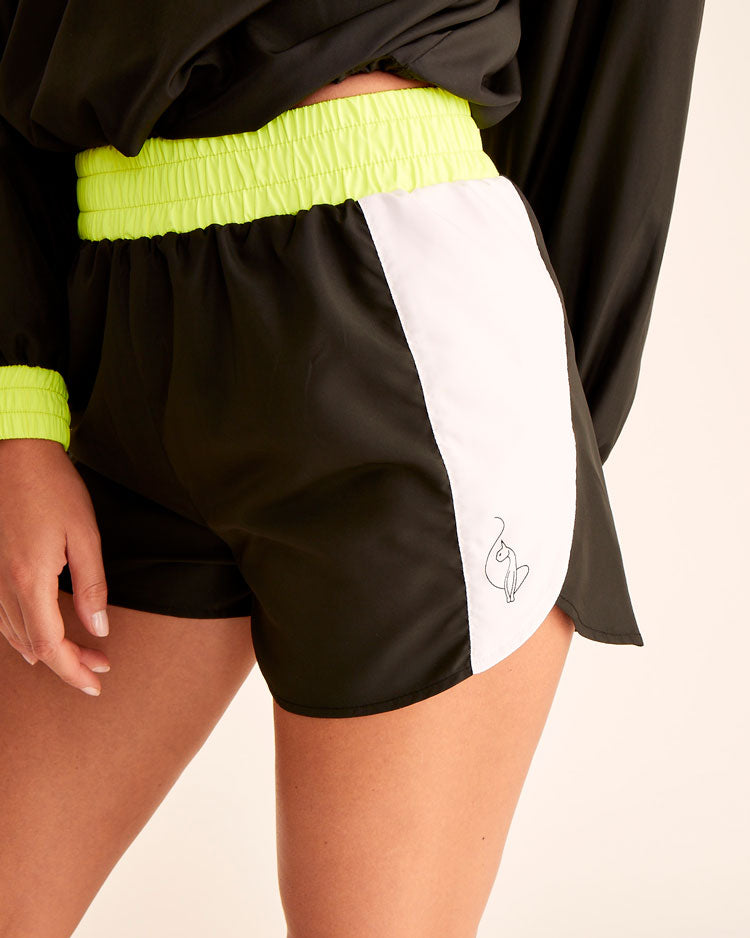 The color block wind shorts are black, white, and neon yellow. Baby Phat logo on one side and cat logo on the other. Elasticized waistband and dolphin short fit.