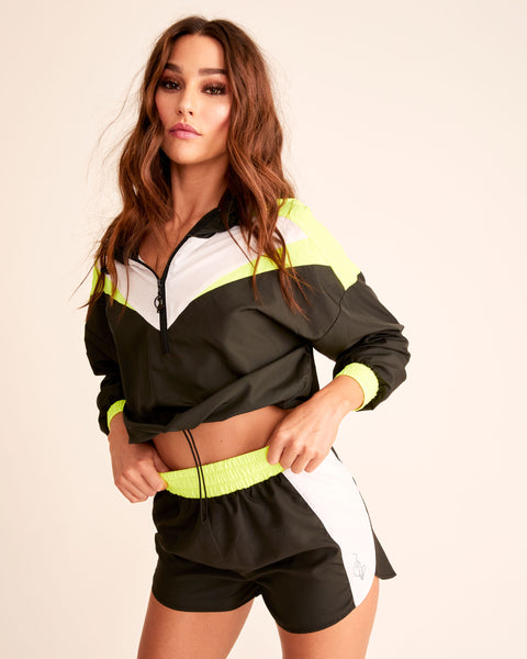 Color blocked, front-zip, long sleeve, black, white, and neon yellow anorak with hood. Baby Phat logo on back, cat charm on zipper, elasticized waist.