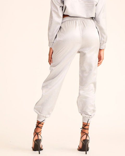 Silver wind pant jogger with reflective piping and Baby Phat logo down the leg. Elasticized drawcord toggle waistband and elasticized leg openings. Loose fit. Pockets.