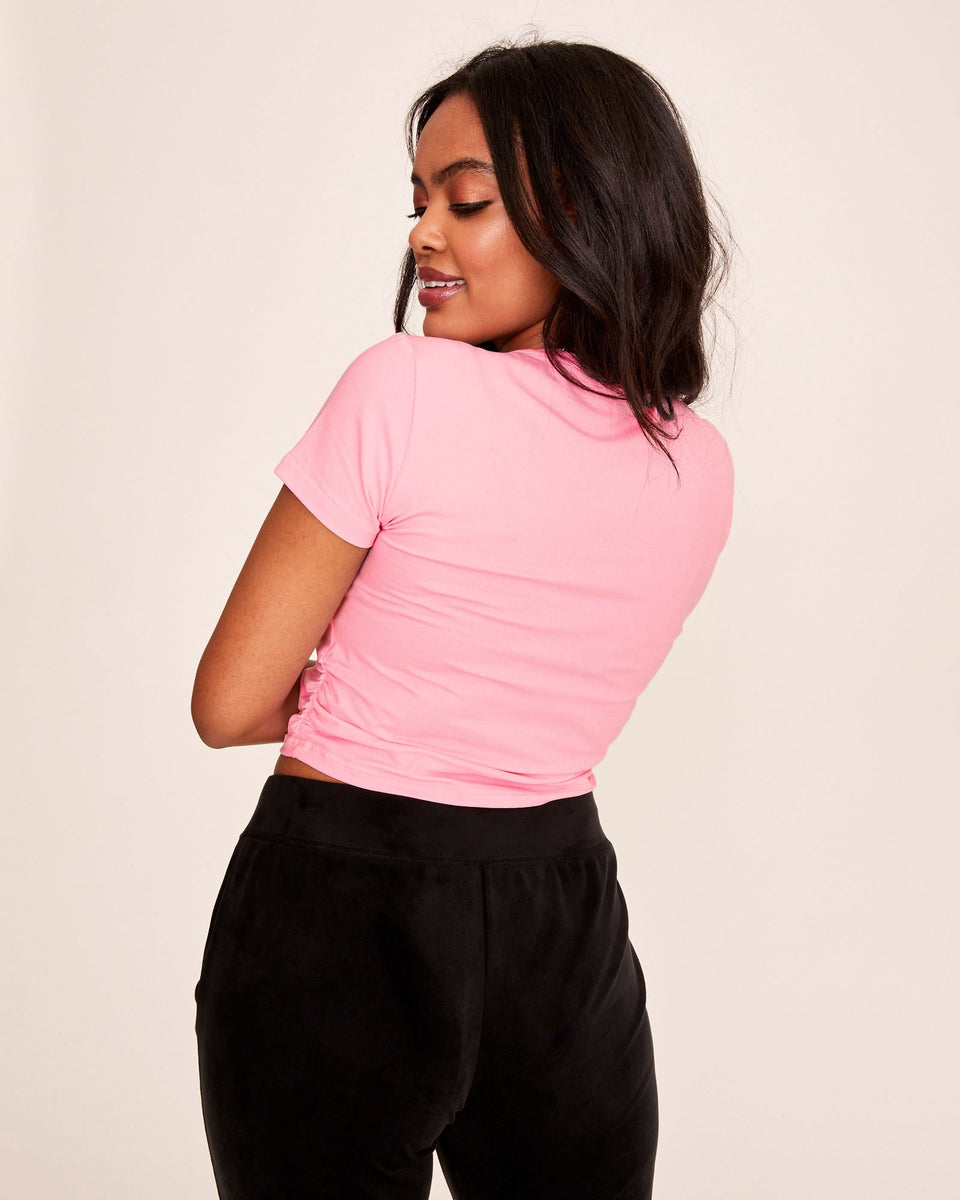 Short sleeved pink cotton t-shirt with Baby Phat silver logo at the front and ruched detailing at the sides. Soft, stretchy fabric and fitted, slightly cropped fit.