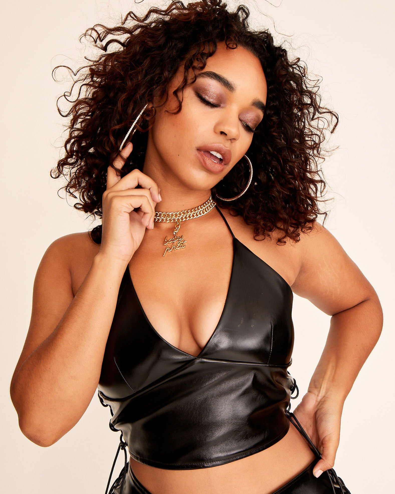 Black vinyl stretch halter with metal Baby Phat cat logo at the back zipper. Lace up sides with metal tip cord.