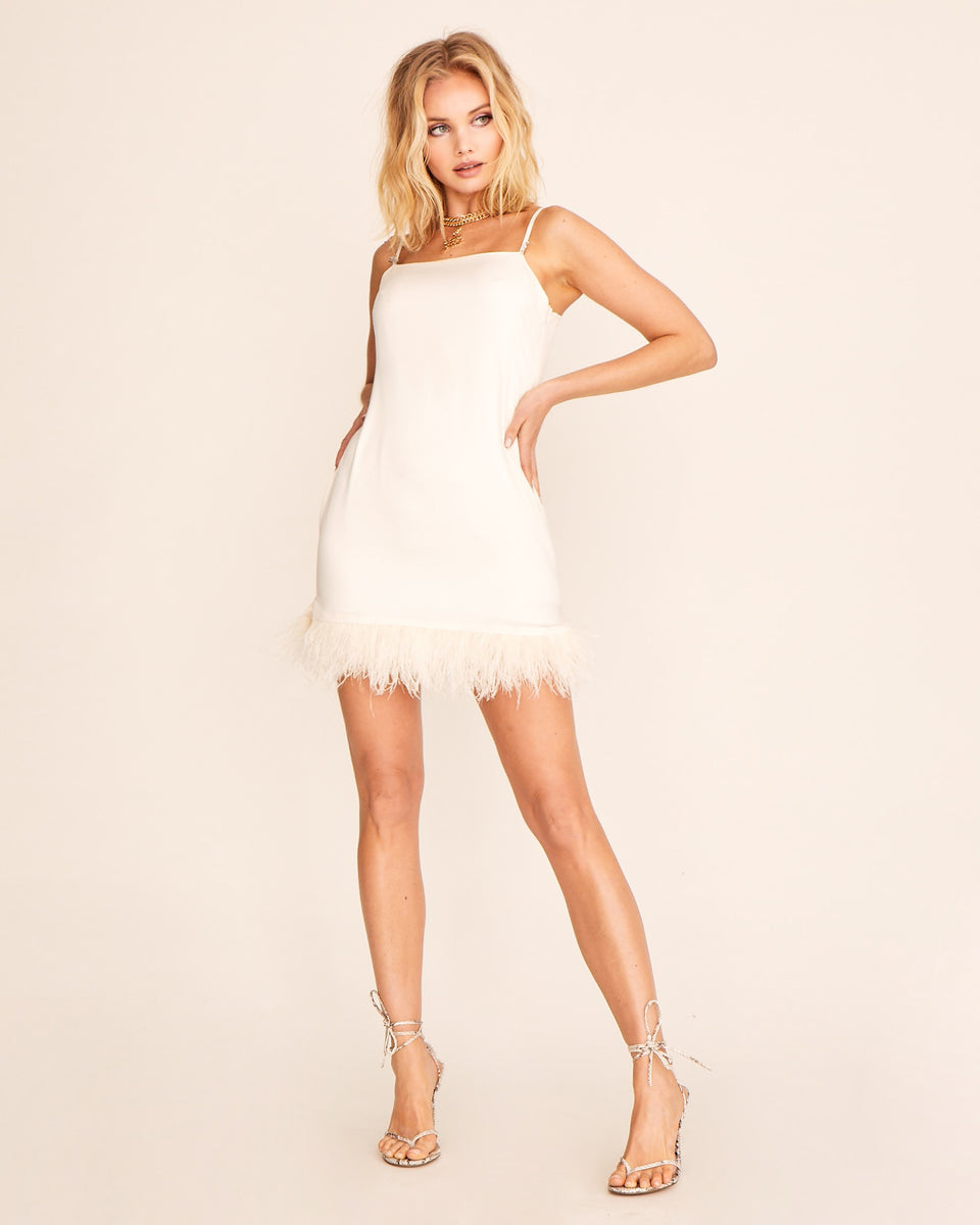 Off white dress featured feathers at the hem and a silky fabric. Features silver Baby Phat logo cat charm on the strap,