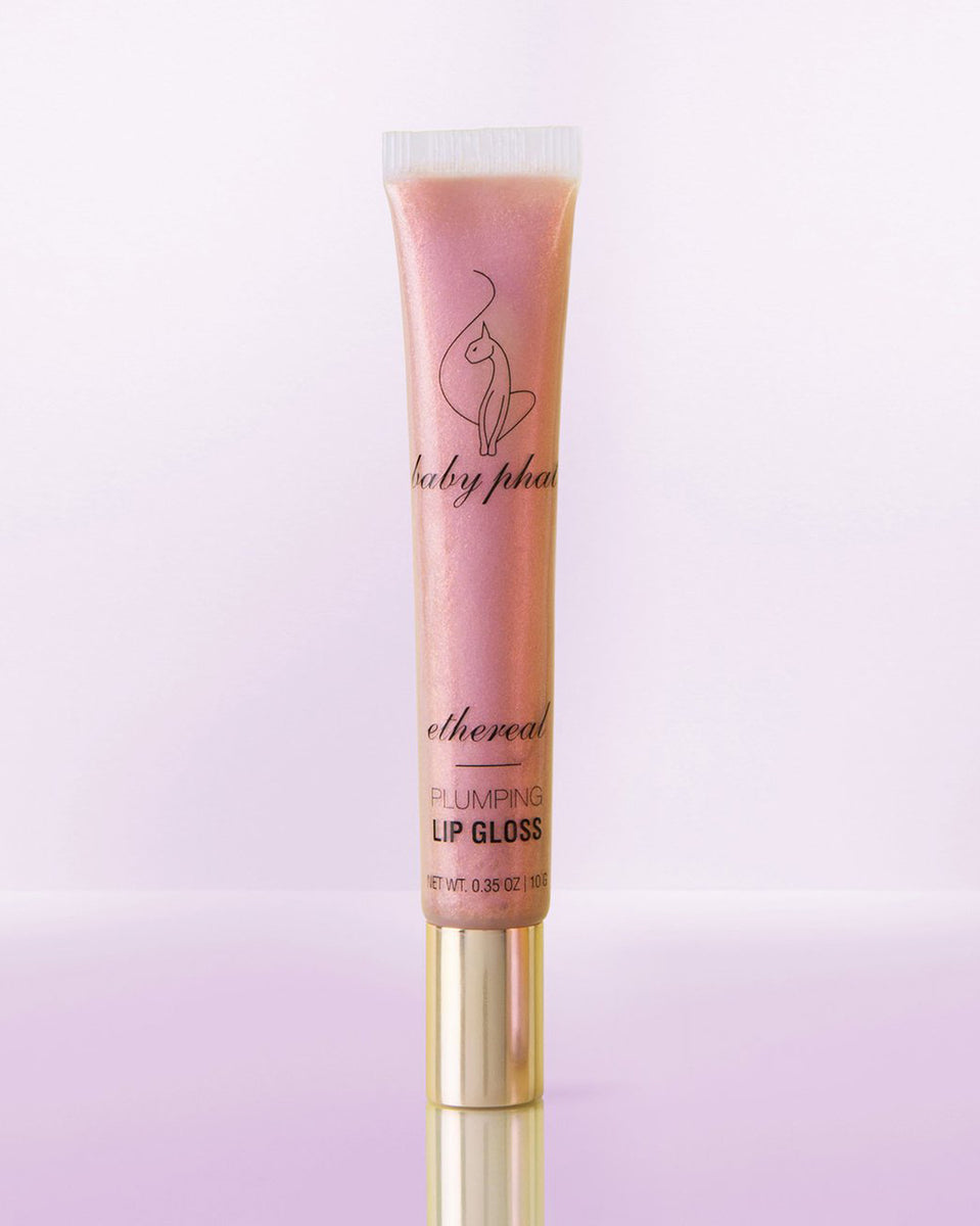 Baby Phat Beauty Plumping Lip Gloss in Ethereal. Glitter lip gloss features metallic gold cap and cat logo at center.