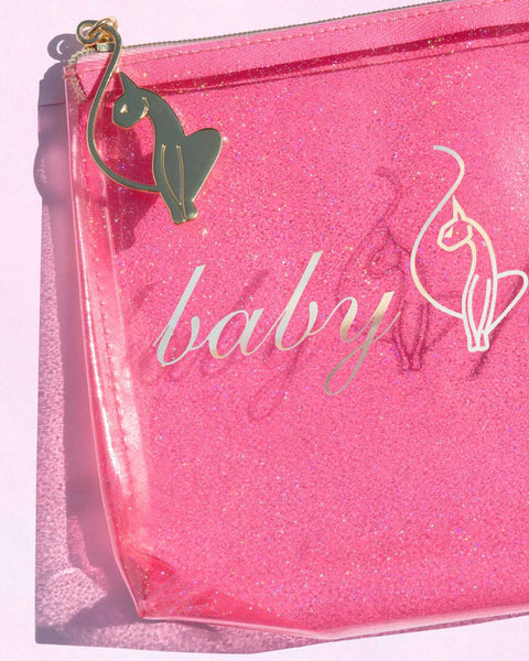 Baby Phat Beauty pink makeup pouch features glitter material and a gold metallic logo at front. Zipper features gold cat charm.