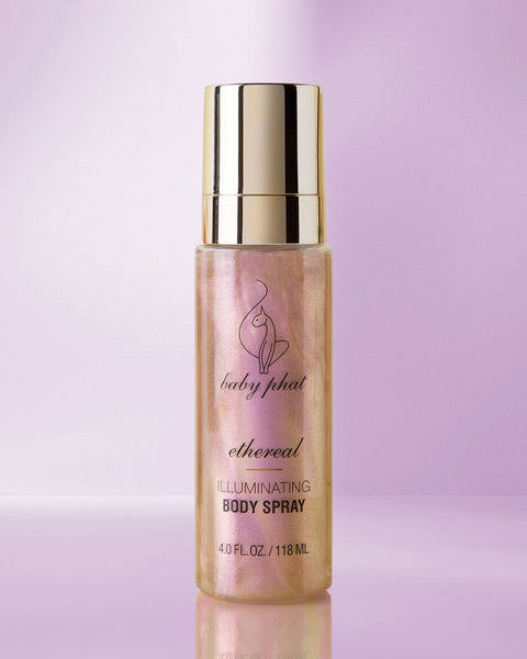 Baby Phat Beauty Illuminating Body Spray in Ethereal. Glitter body spray features metallic gold cap and cat logo on center.