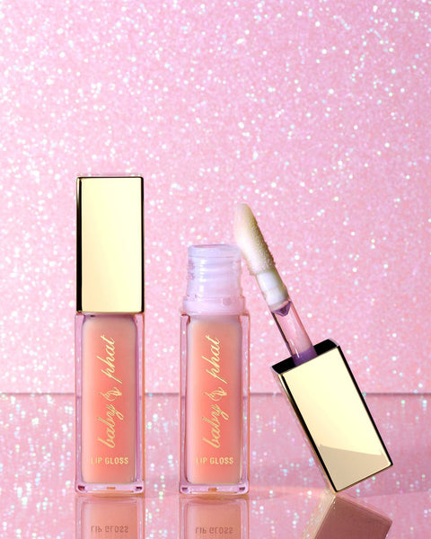 Baby Phat Beauty Limited Edition Pink Glass High-Shine Plumping Lip Gloss features metallic gold cap and Baby Phat script logo across the component. Lip gloss features a sheer pink formula and an oversized applicator.